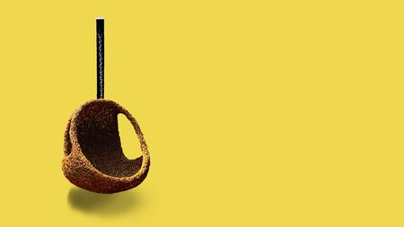 Hanging rattan chair on yellow background.