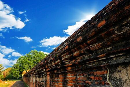 Ancient brick wall in Thailand With blue sky.