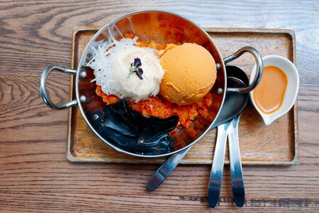 Thai tea ice cream served in stainless steel cups and wooden tray