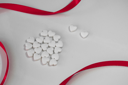 small white heart-shaped tapes on a white background with red ribbon