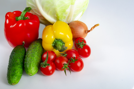 Bulgarian red and yellow peppers on a white background with tomatoes, cabbage, onions and cucumbers healthy lifestyle and proper nutrition concept Banque d'images - 119153183