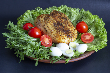 chicken breast on lettuce leaves with tomatoes and quail eggs