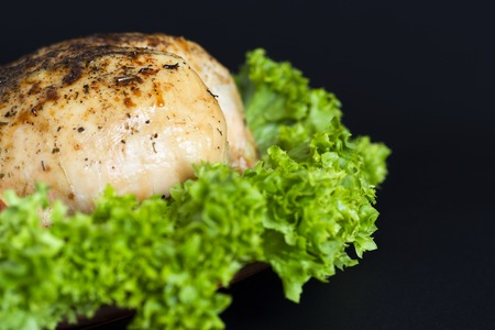 baked chicken breast with green lettuce leaves Фото со стока