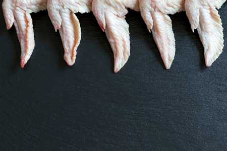 fresh raw chicken wings on a black background cooking healthy food meal