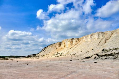 weißer Kalksteinbruch auf einem Hintergrund des blauen Himmels mit Wolken