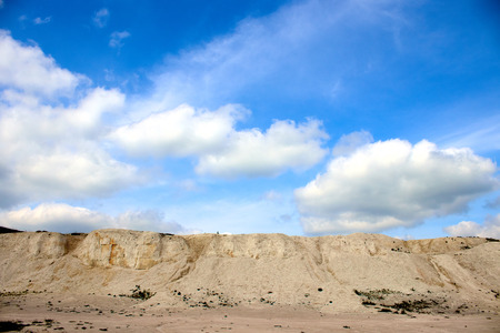 Cantera de piedra caliza blanca sobre un fondo de cielo azul con nubes