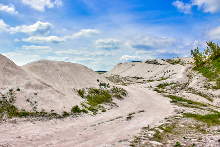 white limestone quarry on a background of blue sky with clouds