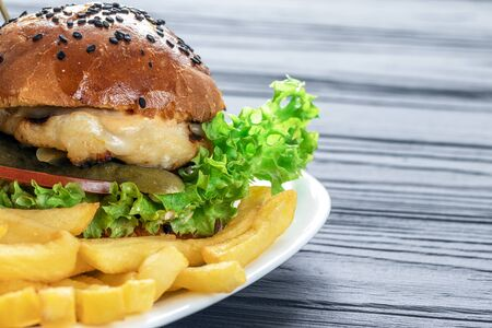 tasty appetizing burger on a white terrel with fries on a gray background fast food high-calorie