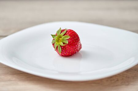 red ripe strawberry on a white plate