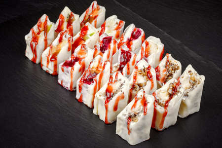 sweet sushi with fruit filling poured with red sauce on a black background