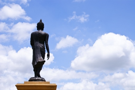 Walking Buddha image statue with cloud and blue sky