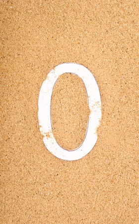 number 0 alphabet made by paper on sand background  photo