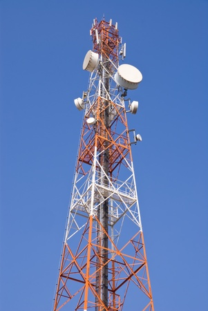 Telecommunication tower with microwave link antennas against blue sky photo
