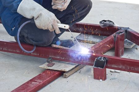 welds: worker welds the pieces of metal together