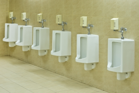 row of urinals in public restroom photo