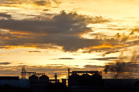 rice mill: smog from smokestack of rice mill against many cloud sunset sky