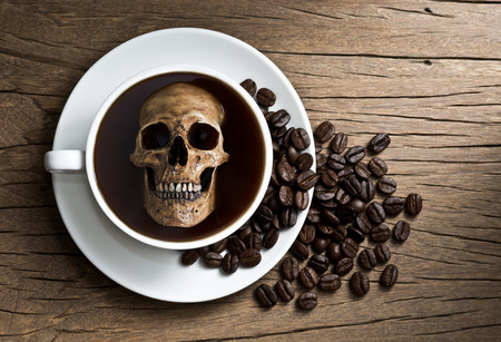 Still life photography, human skull soak in white coffee cup in harmful effect from Caffeine concept Stock Photo