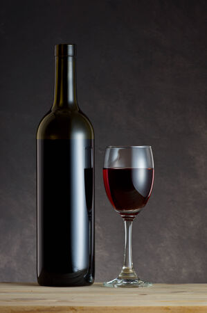 Wine Bottle and glass on wooden table with art dark background Stock Photo