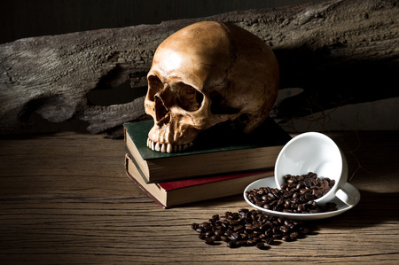 still life photography, coffee beans in white coffee cup with skull and old book on old wood background