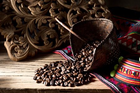 Still life photography, coffee beans from source of production at high mountain plant in northern Thailand  with mini basket, handwork fabric of hill tribe and wood carve background