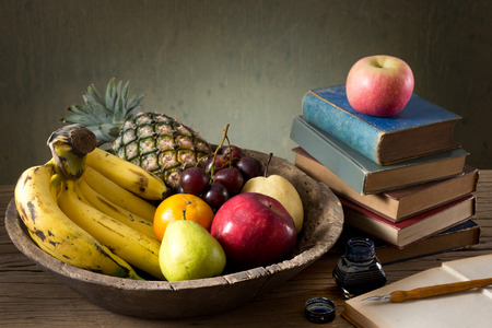 still life photography, many fruit in old wood tray with stacked old book, inkwell and dip pen photo