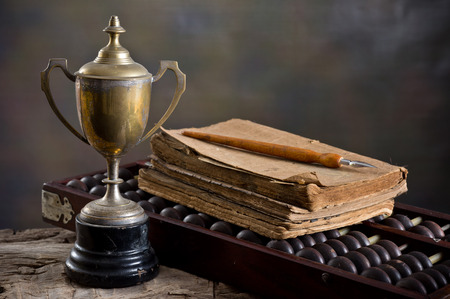 Still life photography, Old trophy with abacus, old book and dip pen Stock Photo