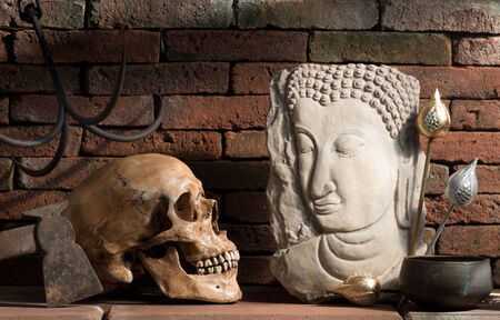 Still life photography, eye contact between buddha image and skull in good and evil concept