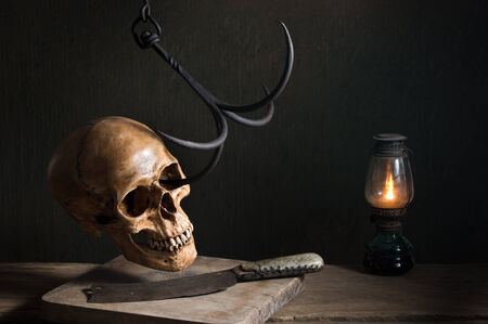 Still life photography, Human skull with steel hook, knife and lantern in murder concept