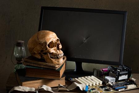 reference book: Photography La naturaleza muerta, cr�neo humano con la placa base, el monitor agrietado y libro de referencia de edad en concepto t�cnico en computaci�n Foto de archivo