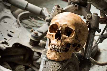 Still life photography, Human skull on front wheel of old motorcycle in junkyard concept