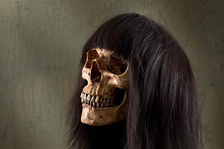 human skull wearing dark brown wig Stock Photo