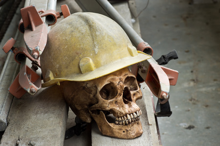 still life photography, Human skull wearing safety helmet with tripod on wood plank in surveyor concept