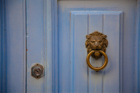 lionhead: A handmade lionhead doorknob on a cyan wood door with his lock