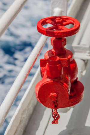 pipe connector: Red fire extinguisher with pipe connector on a boat