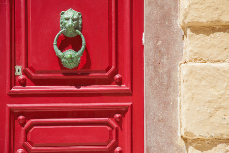 lionhead: A wood red door with lionhead knob and keylock close to a yellow wall
