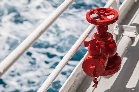 pipe connector: Red fire extinguisher with pipe connector on a boat with waves Stock Photo