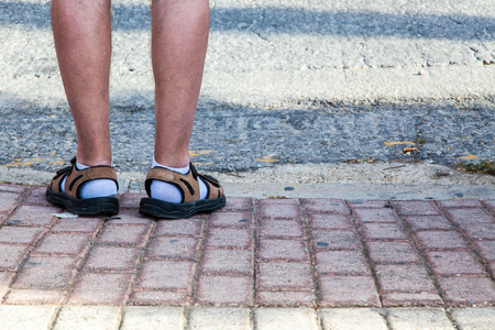 Funny unstyilish feet covered with socks and sandals