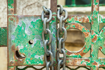 restraint device: A green rusty lock on an iron door with a chain
