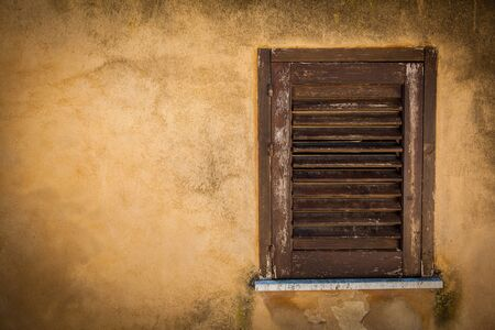 full frame: Closed wood window on an ancient yellow house wall
