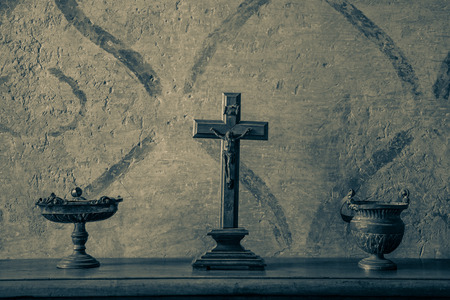 crucifix: An ancient and weathered crucifix on a wood table between bronze vases