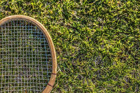Vintage wood tennis racket on grass garden