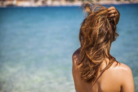 mujer mirando el horizonte: long blonde red hair girl wathckng at the sea with a hand over her head in summer time
