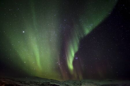 ionosphere: Strong bright green aurora northern lights over mountain, Tromso, Norway