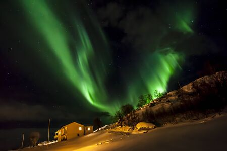 Strong bright green aurora northern lights over mountain, Tromso, Norway