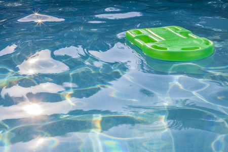 floats: Green lifesaver floating in a swimming pool in summer time with sun reflection