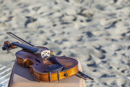 Ancient Violin laying on the beach in summertime Stock Photo