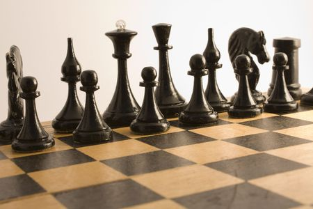 Black chess are placed on a wooden chess board for the beginning games