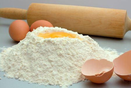 Flour and eggs on a kitchen table for preparation a dough Imagens