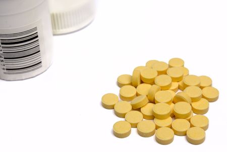 Heap of yellow tablets with a jar on a white background it is isolated Stock Photo - 3945983