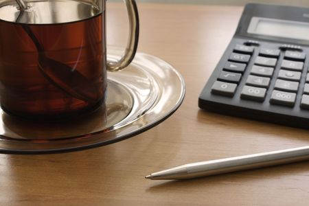 expected: Glass mug with it is expected, the calculator, a pen on a wooden table